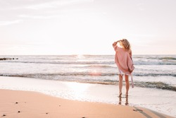 A young slender girl stands alone on the beach or ocean and look at the horizont. A woman dressed in a warm sweater.