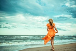 A young slender woman in orange dress is walking barefoot towards the storming sea. The train of her dress is waving. Cool wind in her hair.Outdoor shot. Copy-space.