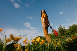 A young slender woman stands against a blue sky in a yellow field, bottom view. Freedom from allergies.