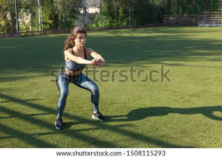 A young slim athletic girl in sportswear with snakeskin prints performs a set of exercises. Fitness and healthy lifestyle. Performs a stretching exercise after the end of the exercise.