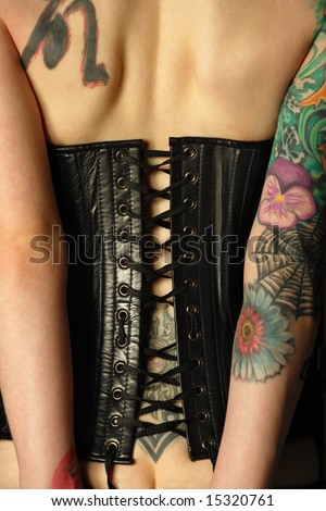 stock photo : A young slim women with arm and back tattoos dressed in a