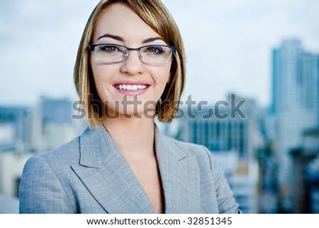 A young smiling businesswoman in a downtown setting