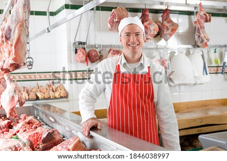 A young smiling butcher wearing a red apron standing next to a meat display case. Foto stock ©