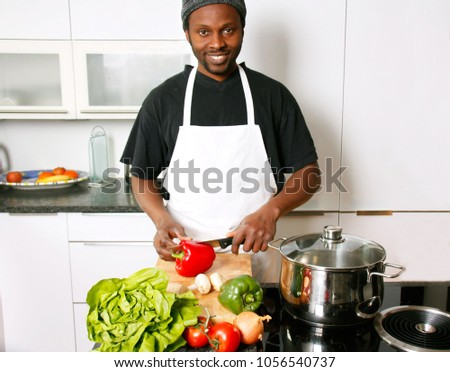 A young smiling chef cooking in the kitchen #1056540737