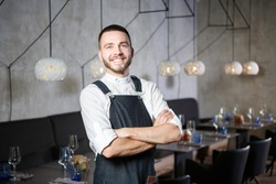 A young, smiling waiter in a restaurant, standing next to the tables with a glass of wine. He wears an apron, looks confidently, folded his arms over his chest