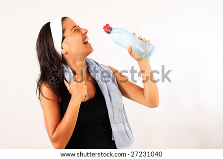 A young smiling woman drinking water after gym. Copy space.