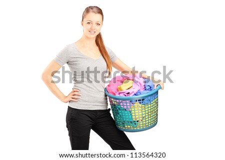 A young smiling woman holding a laundry basket full of clothes isolated on white background