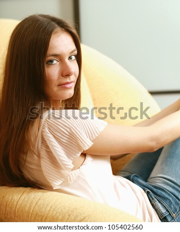 A young smiling woman sitting on the sofa at home
