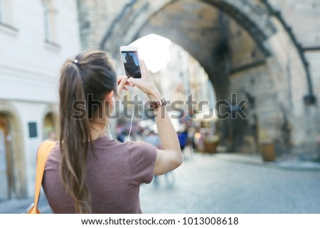 a young smiling woman tourist in sportswear walking in the center of Prague with a phone and taking photo and selfie. travel guide, tourism in Europe, woman tourist with smartphone on the street Сток-фото ©