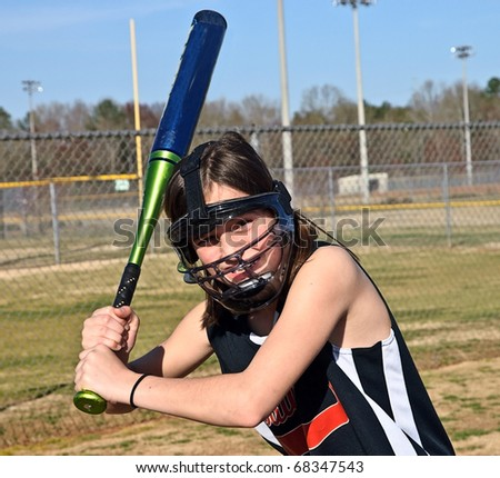 A young softball player with safety equipment on ready to hit the ball.