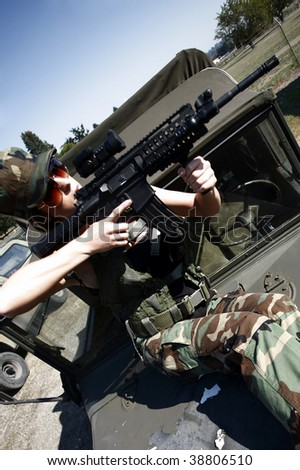 A young soldier aiming an assault rifle.