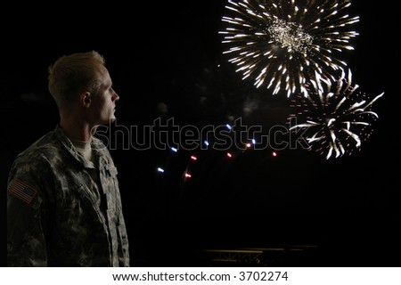 A young soldier watches while fireworks blow in the wind
