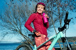 A young sportswoman is drinking water to refresh herself. She is outside on a summer day with a modern bicycle