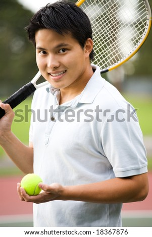 A young sporty casual Asian male playing tennis