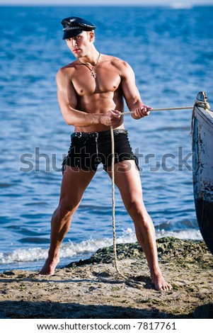 a young stripper posing on the beach as a sailor