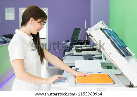 A young student at a copy center taking some copies for her final exams  #1155960964