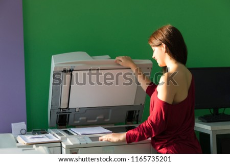 A young student at a copy center taking some copies for her final exams  #1165735201