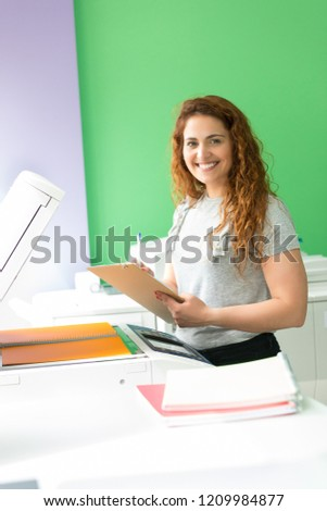 A young student at a copy center taking some copies for her final exams  #1209984877