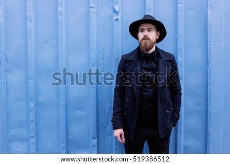 A young stylish bearded hipster in a hat and coat on the street. man enjoying city and standing on blue wall background