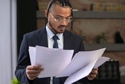A young stylish black unusual office employee examines the received documents, carefully examines them. Young boss with an unusual appearance in the office