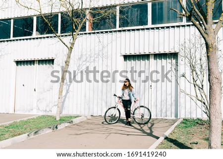 a young stylish girl holds a pink Bicycle standing next to her, against the background of a light hangar on a Sunny spring day