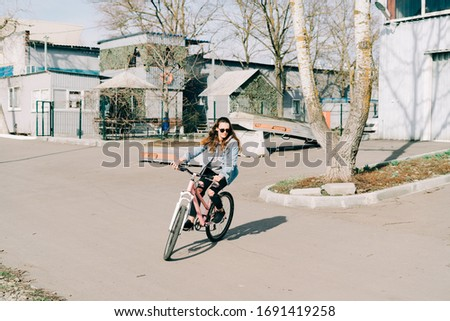 a young stylish girl on a pink Bicycle , riding near a bright hangar on a Sunny spring day