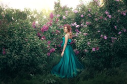 A young stylish model girl in a beautiful fashionable long green dress stands in a summer park near lush flower bushes and looks back