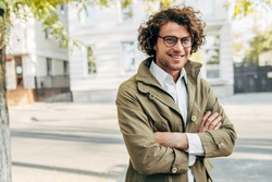 A young successful businessman in eyewear smiling broadly posing outdoors. Male entrepreneur resting in the city street. Smart guy in casual wears spectacles with curly hair walking outside after work