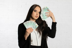 A young successful woman is holding a large amount of cash.