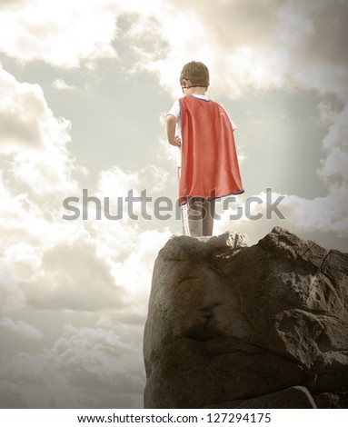 A young super hero boy is wearing a red cape and standing on a rocky cliff looking at a cloudy sky with copyspace.