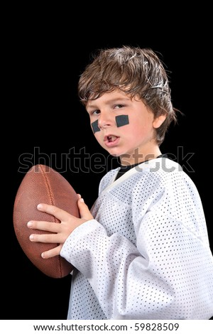 A young, sweaty quarterback football player holds his football and gives an attitude.