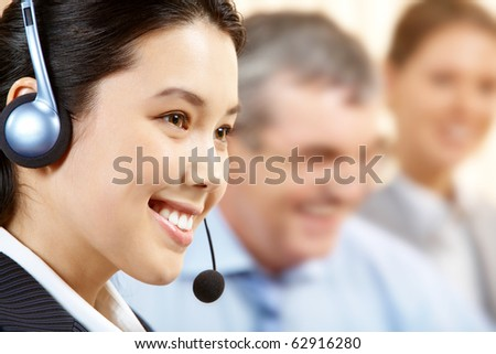 A young switch operator smiling against her two colleagues - stock photo