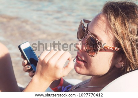 A young tanned woman looks and laughs into a smartphone through sunglasses on a lounger. The concept of a lifestyle is always on the Internet. #1097770412