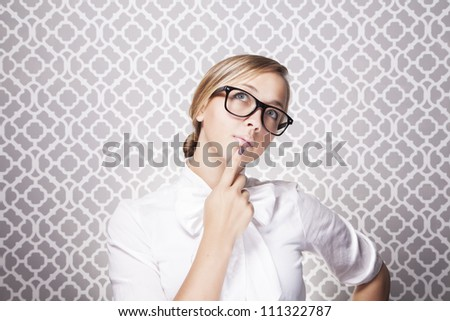 A young teacher or student wearing glasses is in in deep thought while standing in front of a modern pattern.