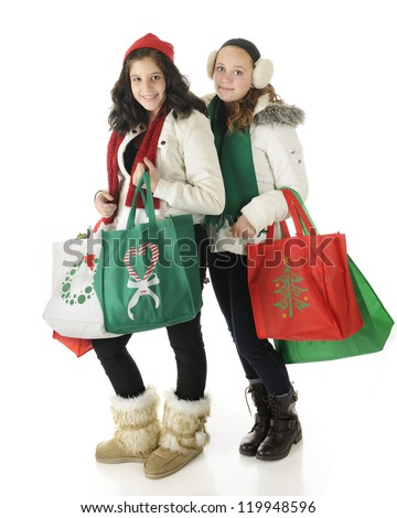 A young teen and her preteen friend dressed for winter and carrying filled Christmas shopping bags.  On a white background.