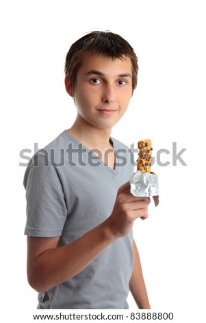 A young teen boy holding a nutritional cereal snack bar.