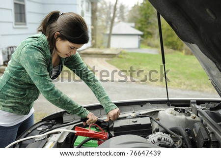 A young teen girl jumping her Dad's car in a middle-class neighborhood.