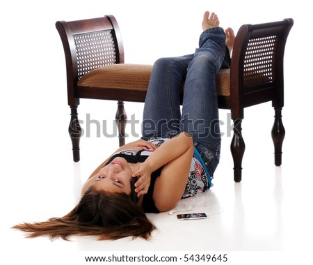 A young teen girl using a cell phone while relaxed on the floor with her barefeet elevated.  Isolated on white.