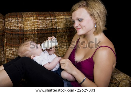 A young teenage girl babysitting a baby boy.