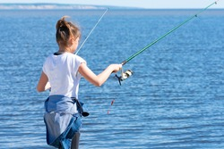 A young teenage girl stands on the Bank of the river and holds a spinning rod in both hands, fishing. Morning fishing. A girl fishing with a fishing rod near the river.