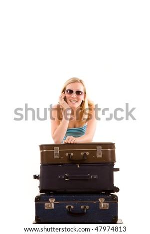 A young teenage girl with sunglasses, leans on a stack of suitcases.  White background
