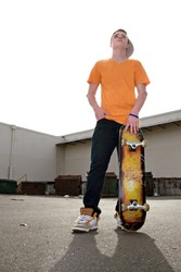 A young teenage skateboarding standing with his skateboard in an urban setting.