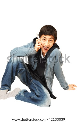A young teenager boy on the cell phone is very happy about the message he gets, on white background.