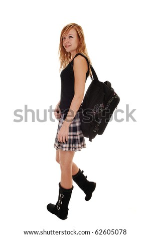 A young teenager in a skirt and black boots with her back bag over her shoulder, standing from the back, and looking over her shoulder,  for white background.