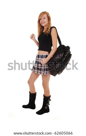 A young teenager in black boots and a short skirt with her back bag over her shoulder on the way to school, on white background.