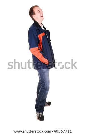 A young teenager in jeans and blue and orange jacket standing in the studio and laughing, for white background isolated.