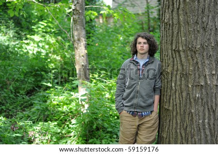 A young teenager leans up against the tree in the forest, looking out into the distance.