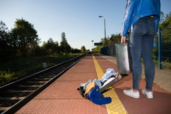 A young teenager's travel suitcase unfastened accidentally at a train station. Unlucky holiday at the train station.