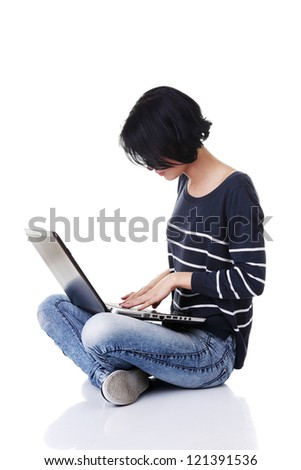 A young thoughtful woman with a laptop sitting isolated on white background