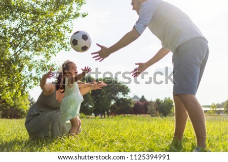 A young three-member family spends the afternoon in the park and plays with a soccer ball. Family runs out together. Family leisure activities. Three members family playing with a ball on the meadow.